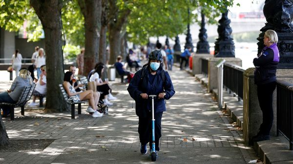 File photo - A woman wearing a protective face mask rides a scooter along the South Bank in London. (REUTERS)