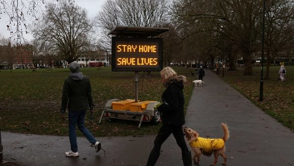People walk past a newly placed sign on Eel Brook Common as EU countries impose a travel ban from the UK. (REUTERS)