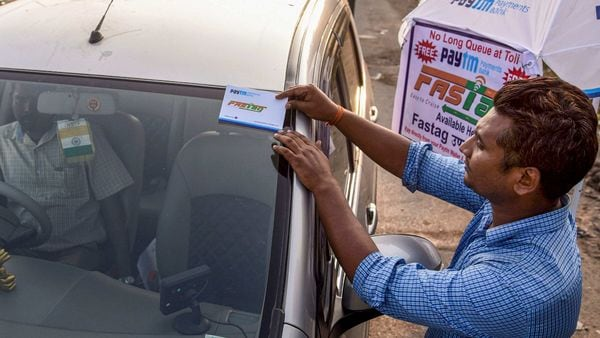 File photo of a person attaching a FASTag sticker to a vehicle. (PTI)