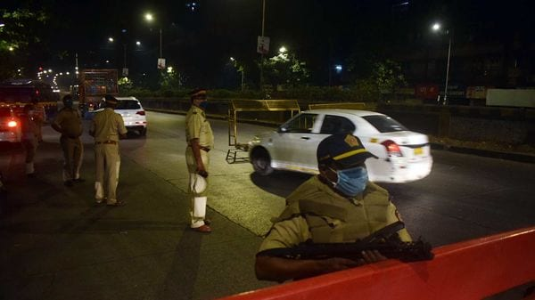 Police personnel stand guard as night curfew was imposed by the Government of Maharashtra at Dadar in Mumbai.