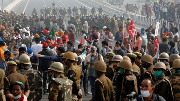 Farmers block a highway as police officers stand guard during a nationwide strike against the newly passed farm bills at the Delhi-Uttar Pradesh border in Ghaziabad. (REUTERS)