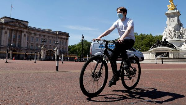A man wearing a protective face mask cycles past Buckingham Palace, following the outbreak of the coronavirus disease in London, Britain. (REUTERS)