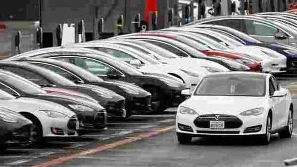A Tesla Model S electric vehicle drives along a row of occupied superchargers. (File Photo) (REUTERS)
