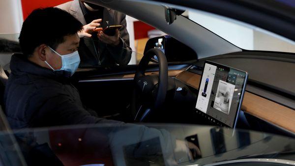 A man checks the touchscreen inside Tesla Model Y sport utility vehicle. (File Photo) (REUTERS)