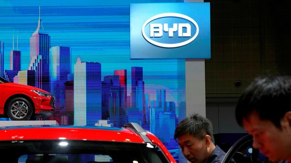 FILE PHOTO: Men clean a BYD electric vehicle (EV) e2 displayed during the media day for Shanghai auto show in Shanghai, China (REUTERS)