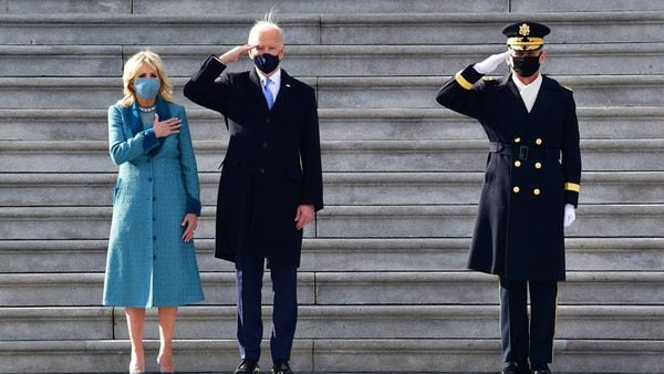 US President Joe Biden (C) salutes as wife US First Lady Jill Biden (L) holds her hand on her heart on the east steps of the US Capitol. (AFP)