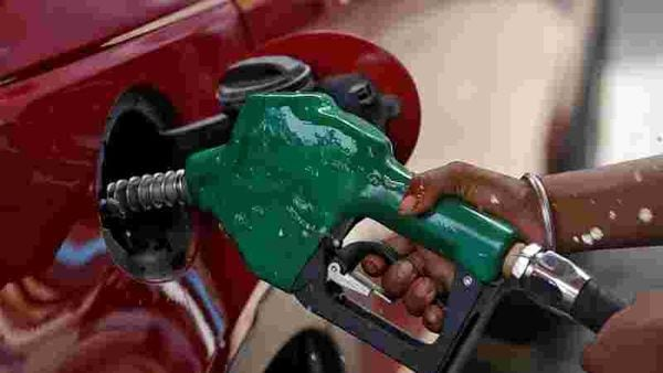 A worker holds a nozzle to pump petrol into a vehicle at a fuel station in Mumbai. (REUTERS)