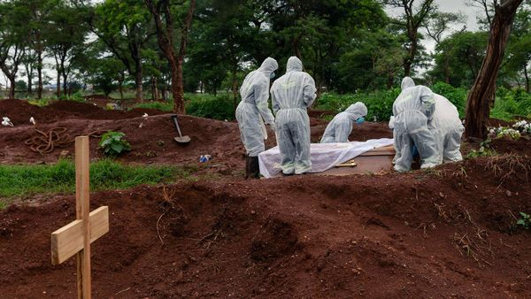 Undertakers in full body personal protective equipment (PPE) lower the coffin of a person who passed away due to Covid-19 in to a grave at Glen Forest cemetery in Harare. (AFP)