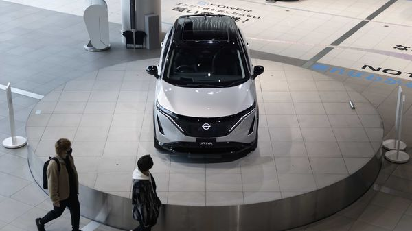 Visitors look at a Nissan Ariya electric crossover sport utility vehicle (SUV) on display inside a showroom. (File photo) (Bloomberg)