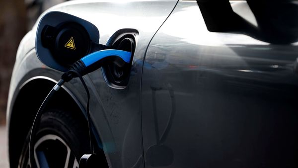 A charging cable is pictured plugged into a Volvo electric vehicle (EV), parked in a parking bay reserved for electric vehicles, in London on November 18, 2020. (AFP)