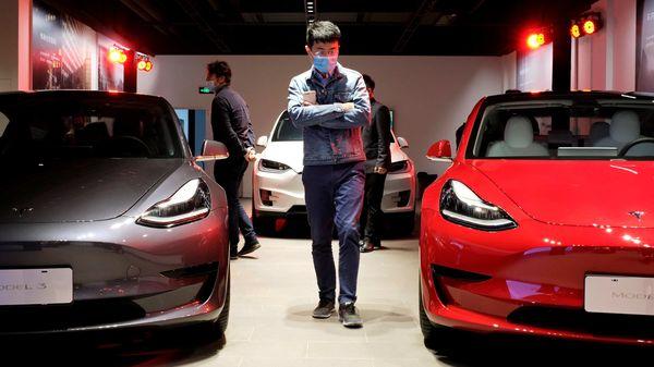 A man walks by Tesla Model 3 sedans and Tesla Model X sport utility vehicle at a new Tesla showroom in Shanghai. (File Photo) (REUTERS)