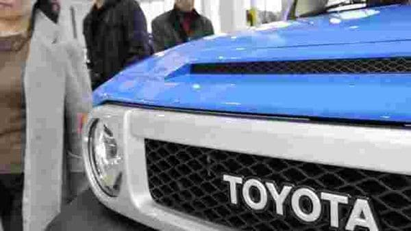 Customers-walking-past-vehicles-at-a-Toyota-showroom-in-Tokyo-Photo-AFP-Yoshikazu-TSUNO