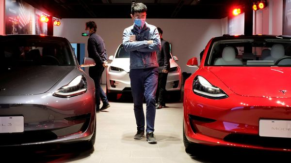 A man walks by Tesla Model 3 sedans and Tesla Model X sport utility vehicle at a new Tesla showroom in Shanghai. (File Photo) (REUTERS)