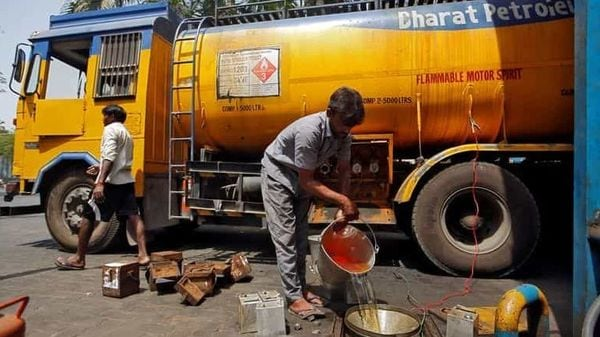 A man pours petrol into an underground tank at a fuel station in Mumbai. (REUTERS)