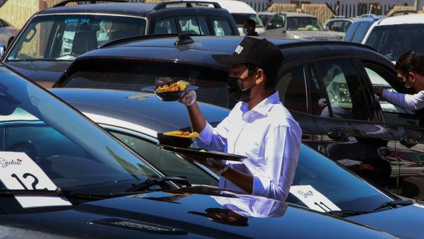 Waiters serve food to customers in their cars outside a restaurant in Kuwait City on March 9, 2021. (AFP)