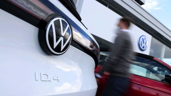 A salesman passes a Volkswagen ID.4 electric SUV on the forecourt of a Volkswagen AG (VW) showroom in Berlin, Germany, on Tuesday, March 16, 2021. Volkswagen plans to widen cost-saving efforts and standardize key technologies as the German manufacturer seeks to rival�Tesla Inc.�on electric cars and keep traditional rivals at bay. Photographer: Liesa Johannssen-Koppitz/Bloomberg (Bloomberg)