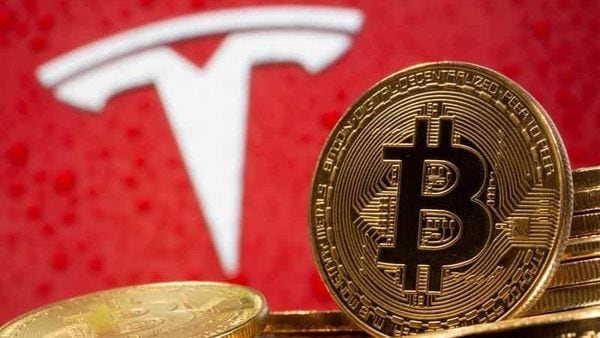 Representations of virtual currency Bitcoin are seen in front of Tesla logo in this illustration. (REUTERS)