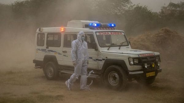 A healthworker waits for relatives to unload the body of a man, who died from the coronavirus disease (COVID-19), for burial. (REUTERS)