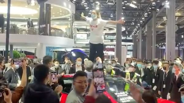 Screengrab from the video which shows a woman on top of a Tesla Model 3 at the Shanghai Auto Show. (Photo courtesy: Twitter/globaltimesnews)