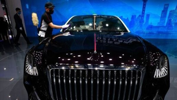A worker cleans the surface of a car from Chinese luxury auto brand Hongqi's L-Concept car at the Shanghai Auto Show 2021. (AP)