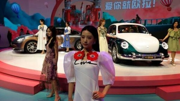 Models pose for photos with the latest cars from Chinese auto brand Ora at the Auto Show. (AP)
