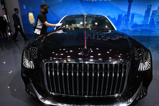 A worker cleans the surface of a car from Chinese luxury auto brand Hongqi's L-Concept vehicle. The concept car comes in a three-seat format without a steering wheel. (AP)