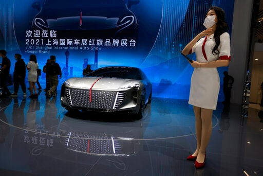 A promoter stands near a concept car for Chinese luxury auto brand Hongqi. which is China's oldest automotive manufacturer. (AP)