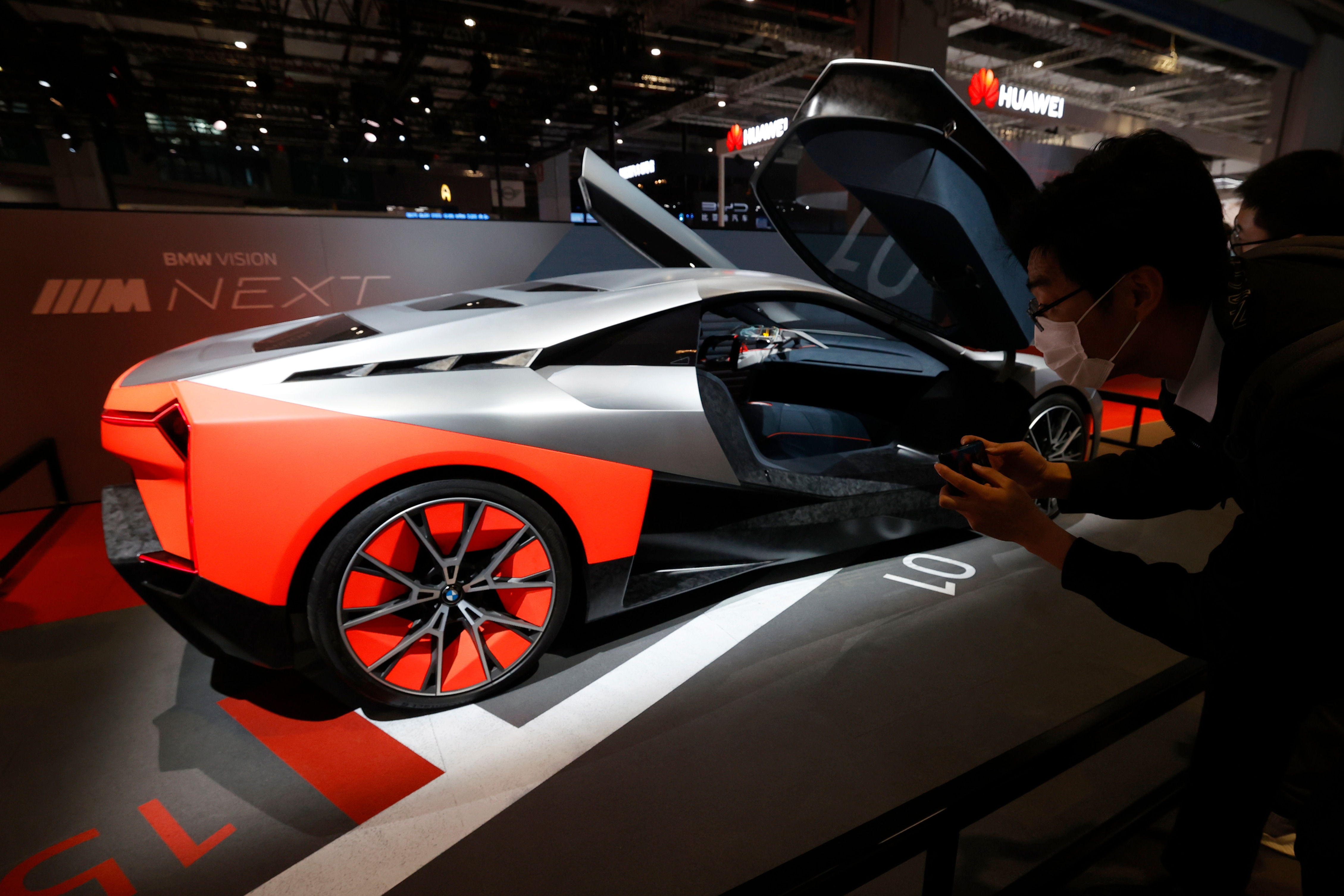 A visitor looks at the BMW Vision Next concept car displayed at the BMW booth. He can be seen clicking pictures of the concept vehicle. (AP)