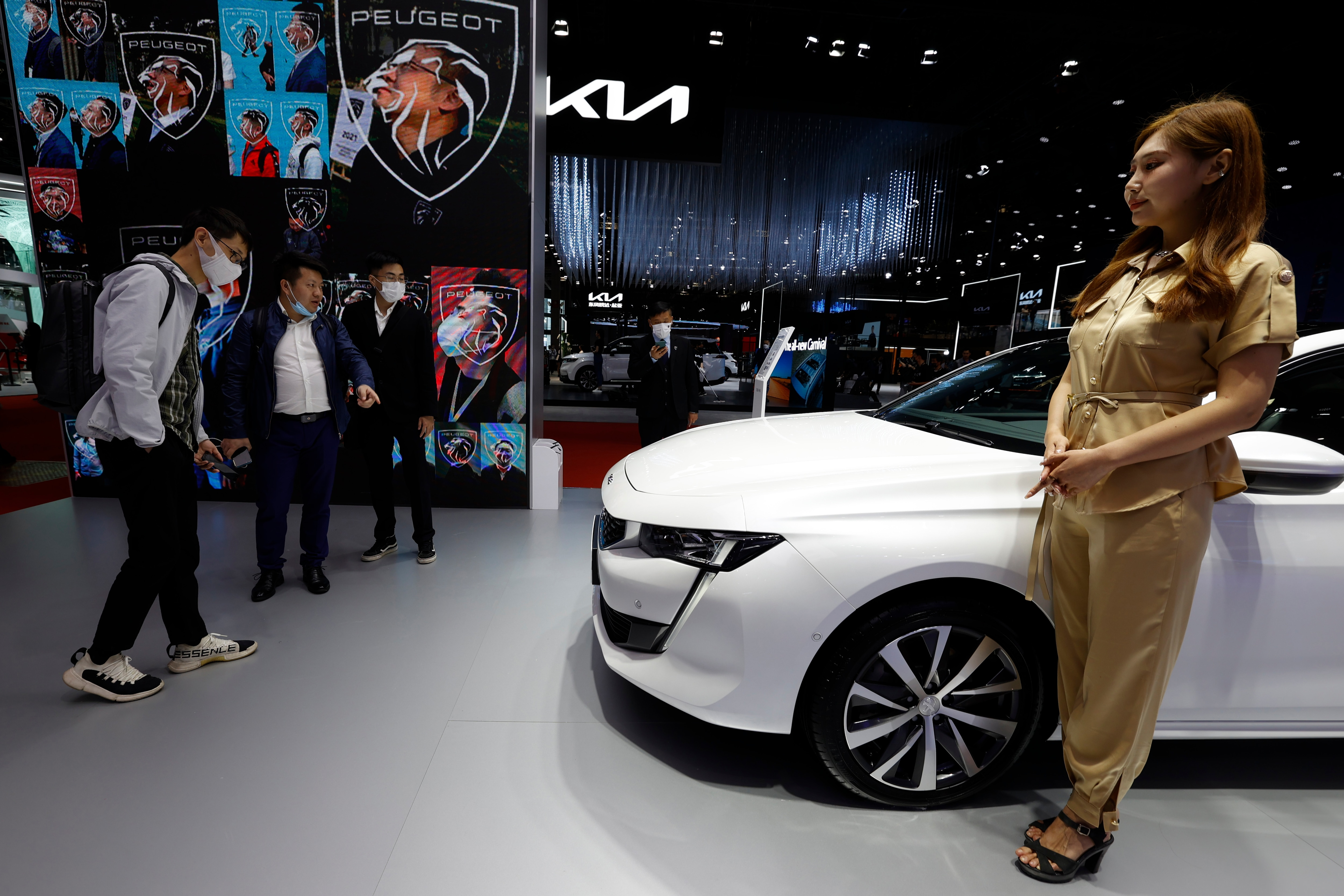 Visitors look at the latest cars on display at the Peugeot booth while a promoter stands next to a vehicle. (AP)