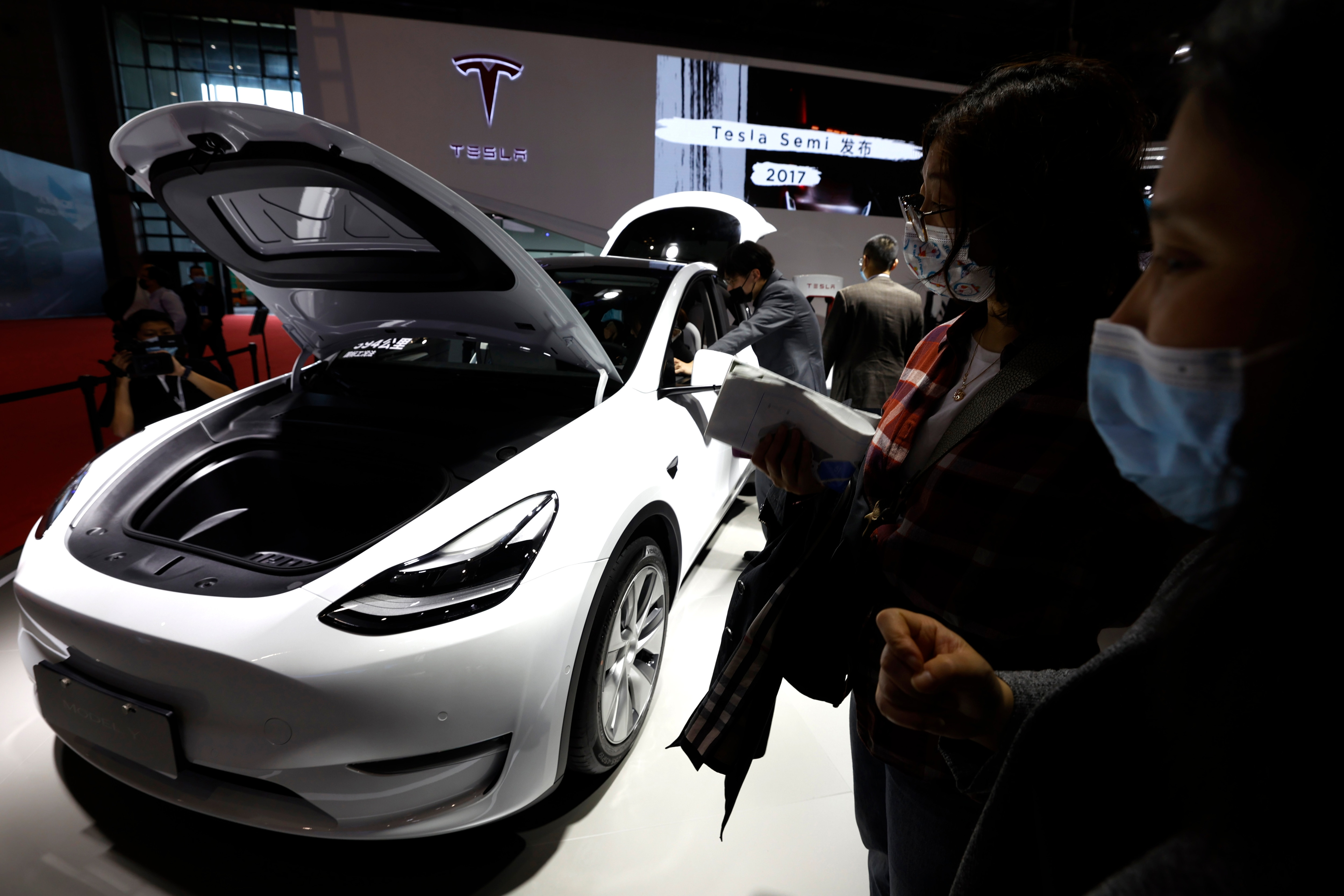 Visitors check out vehicles displayed at the Tesla booth during the Shanghai Auto Show. (AP)
