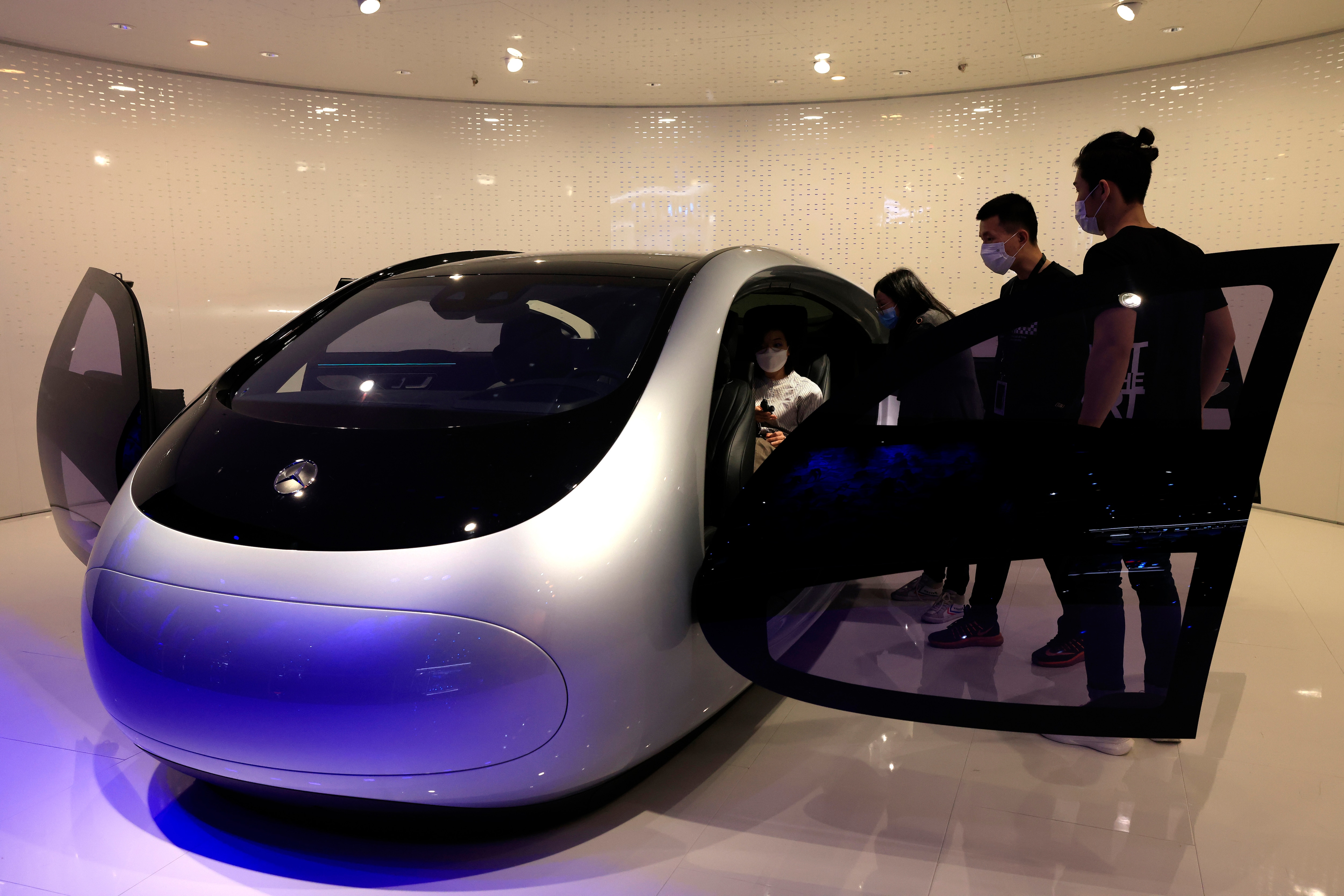 Visitors try out a concept vehicle at the Mercedes-Benz booth. While some steep inside the concept car to experience its ambience, some look at it from outside. (AP)