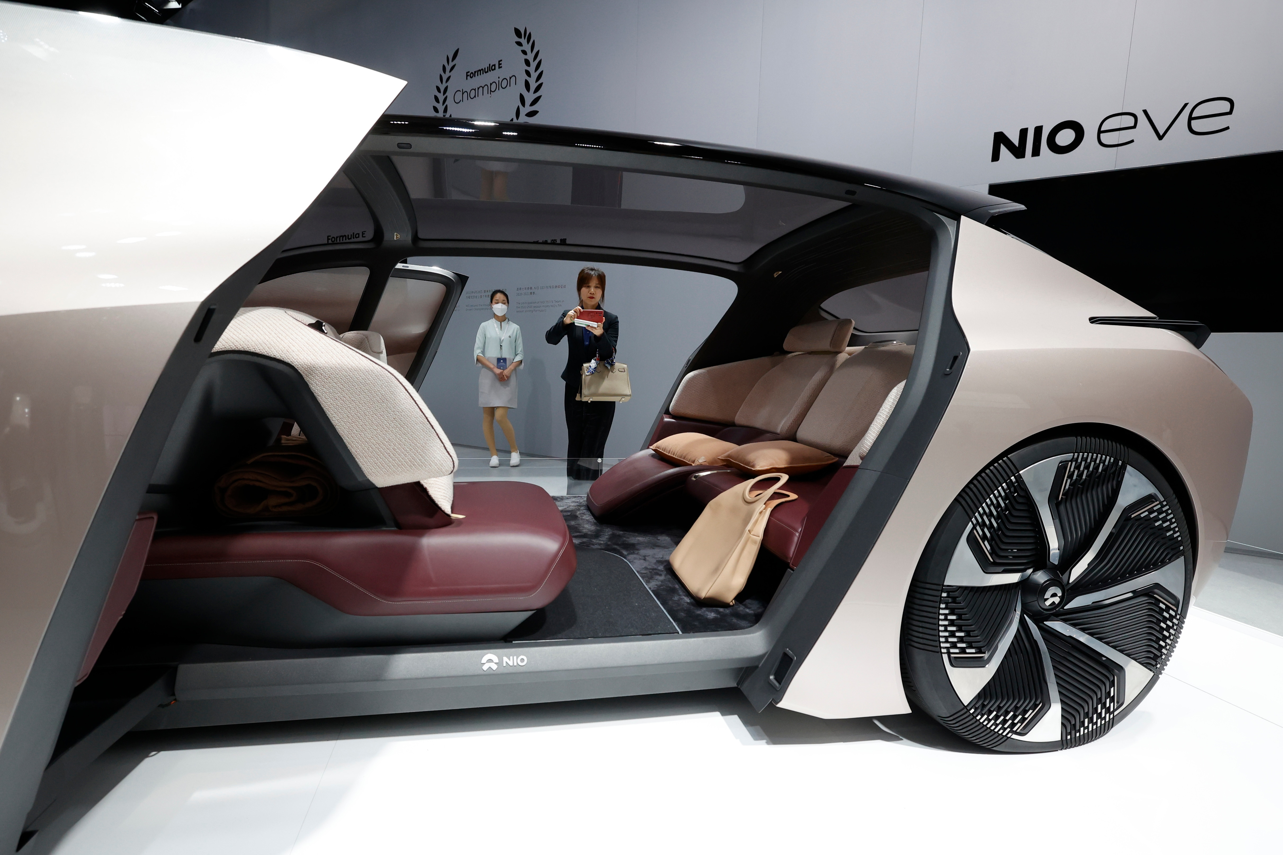 NIO has displayed its eve concept car at the Auto Show, A female visitor can be seen clicking pictures of the concept vehicle that seems to have huge interior seating space. (AP)