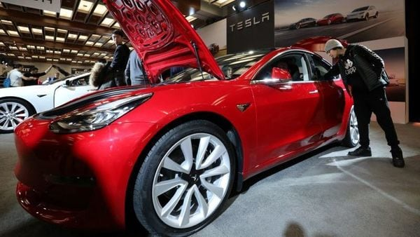 A customer takes a look at Tesla Model 3 electric vehicle. (Picture credit: Reuters)