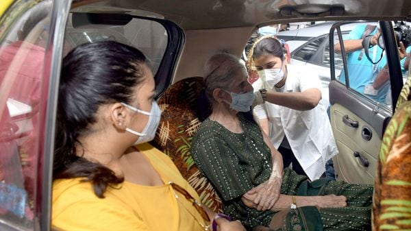 A medic inoculates the dose of the Covid-19 vaccine to a beneficiary during a drive-in-car vaccination drive, at Dadar in Mumbai.