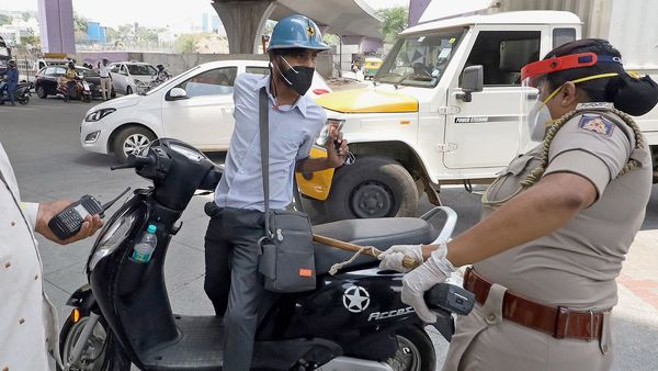 A police woman punishes a scooterist for flouting Covid-19 lockdown rules in Bengaluru on Saturday, May 8, 2021. (PTI)