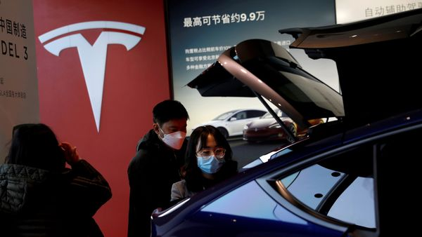 Visitors wearing face masks check a China-made Tesla Model Y sport utility vehicle at the electric vehicle maker's showroom in Beijing. (File Photo) (REUTERS)
