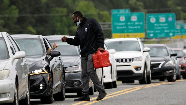 A person carrying a fuel container is greeted by a motorist waiting in a lengthy line to enter a fuel station during a surge in the demand for fuel in Durham, North Carolina. (REUTERS)