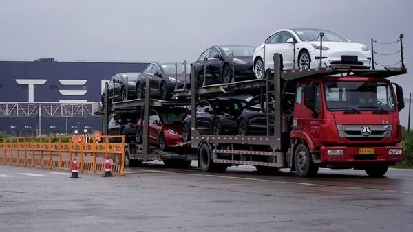 A truck transports new Tesla cars at its factory in Shanghai, China. (REUTERS)