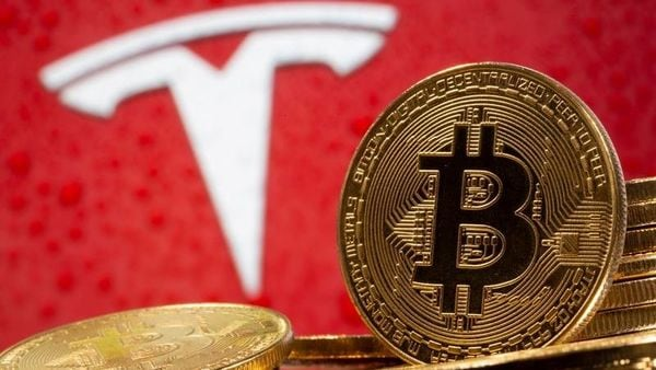 Representations of virtual currency Bitcoin are seen in front of Tesla logo. (REUTERS)