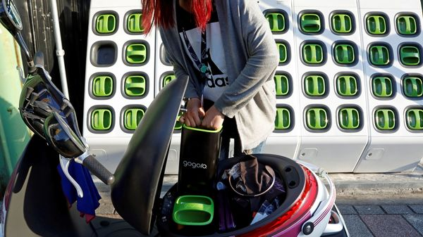 A woman charges battery of her electric scooter at the Gogoro's charging station in Taipei, Taiwan. (File photo) (Reuters)