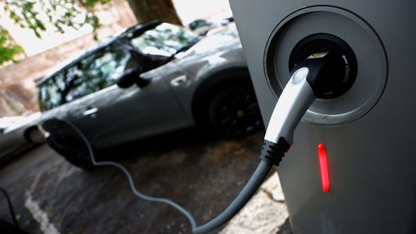 FILE PHOTO: An electric car is seen plugged in at a charging point for electric vehicles. (REUTERS)