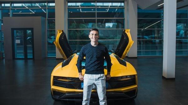 Juventus Striker Paulo Dybala poses with the Lamborghini Aventador he received.