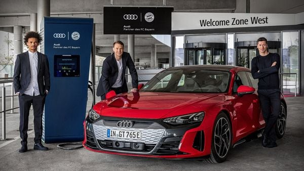 Bayern Munich footballers Leroy Sane, Manuel Neuer and Robert Lewandowski with an Audi e-tron GT recharging from one of the charging points set up by the football team along with the car manufacturer.