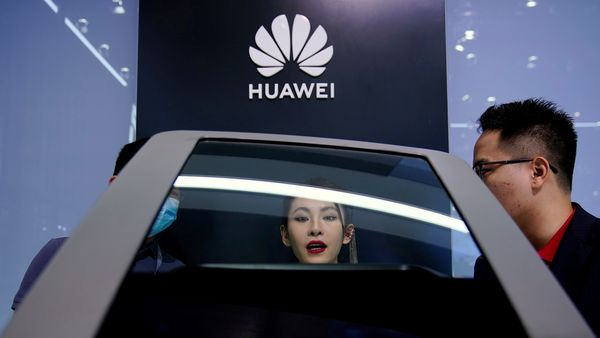 File photo: People check a display near a Huawei logo during a media day for the Auto Shanghai Show in Shanghai. (REUTERS)