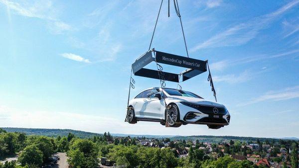 The Mercedes EQS all electric sedan dangling over the Stuttgart tennis court. (Daimler)