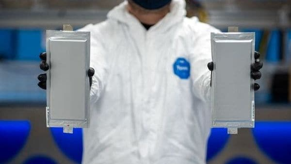 A Solid Power manufacturing engineer holds two 20 ampere hour (Ah) all-solid-state battery cells for the BMW Group and Ford Motor Company. (via REUTERS)