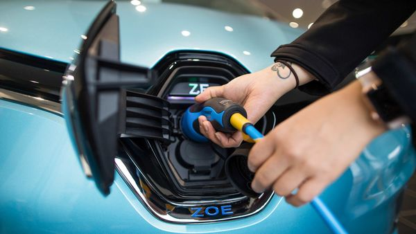An employee places the electric charger into a new Renault Zoe automobile, manufactured by Renault SA. (Bloomberg)