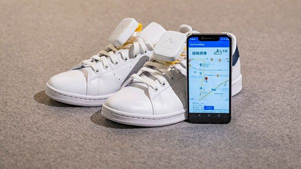 Ashirase vibration device attached to shoes and its smartphone app screen. (Honda)