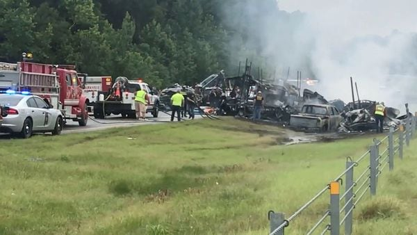 Emergency personnel work at the accident site as smoke rises from the wreckage after several vehicles slammed together on a rain-drenched Alabama highway. (via REUTERS)