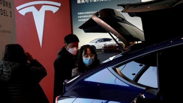 File photo: Visitors wearing face masks check a China-made Tesla Model Y SUV at a showroom in Beijing. (REUTERS)